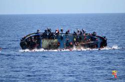 Uprchlíci se snaží dostat z převracející se lodě