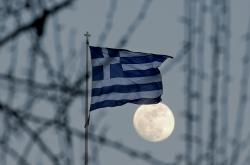 Řecká vlajka vlaje za svitu měsíce v Aténách