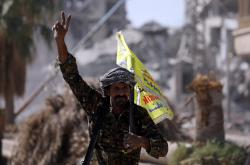 Vítězné gesto bojovníka arabsko-kurdských milic