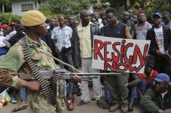 Voják kontroluje dav Zimbabwanů oslavujících Mugabeho pád