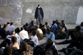 Policista v Tripolisu dohlíží na nelegální migranty