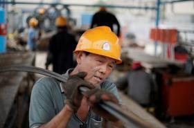 Čínský dělník nese ocelové tyče