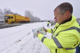 Mluvčí ŘSD ukazuje fotografii velké kaverny, která vznikla při opravách dálnice