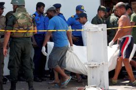 Muži odnášejí oběť výbuchu u kostela svatého Antonína