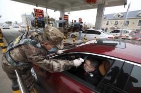 Příslušník bezpečnostních složek měří teplotu řidiči na kontrolním stanovišti ve Wu-chanu