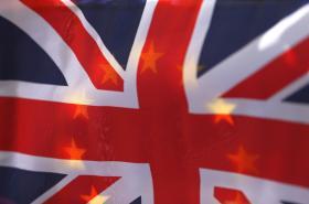 Vlajka Velké Británie a v pozadí prosvítající vlajka EU