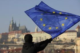 Muž s vlajkou Evropské unie - v pozadí panorama Pražského hradu