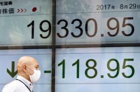 Muž prochází v Tokiu kolem elektronické tabule s akciovými indexy.