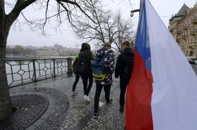 Lidé s českou vlajkou procházejí po Smetanově nábřeží v centru Prahy.