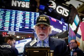 Obchodník na parketu newyorské akciové burzy NYSE. Jeho čepice připomíná překonání hranice 24 000 bodů.
