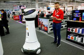 Zaměstnanec s tabletem kontroluje robota Paula, který zákazníkům například pomáhá najít zboží.