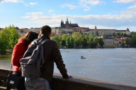 Turisté hledící na panorama s Pražským hradem a řekou Vltavou.
