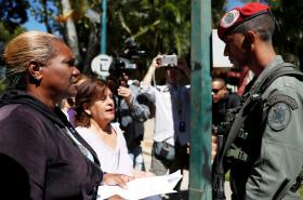 Zastánkyně opozičního hnutí hovoří s členem ochranky prezidentského paláce