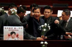 Prodemokratický poslanec je vyváděn z jednací síně hongkongského parlamentu