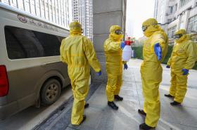 Pracovníci pohřební služby v ochranných oblecích ve Wu-chanu