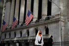 Žena s rouškou před newyorskou akciovou burzou NYSE