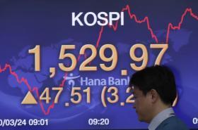 Obchodník před tabulí s křivkou jihokorejského indexu Kospi