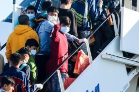 Nezletilí uprchlíci mávají před odletem z Atén do Německa.