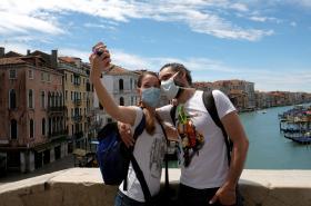 Turisté v rouškách se fotí v benátském centru