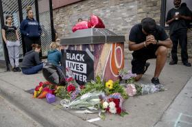 Lidé se shromažďují a modlí u pomníku nedaleko místa, kde černoch později zemřel