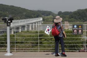 Žena s jihokorejskou vlajkou dívající se směrem na KLDR