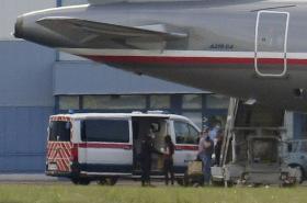 Všelichová s Farkasem nastupují do zdravotní sanitky na letišti ve Kbelích