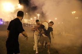 Demonstranti v Minsku odnášejí zraněného muže