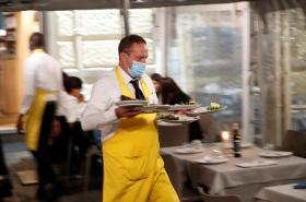 Číšník v roušce v italské restauraci
