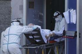 Zdravotníci nesou na nosítkách pacienta nakaženého koronavirem