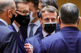 Francouzský prezident Macron mluví na summitu s polským premiérem Morawieckim a maďarským premiérem Orbanem (zády)
