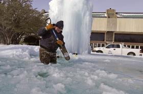 Pracovník služeb texaského města Richardson rozbíjí led v zamrzlé kašně