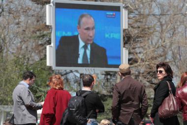 Obyvatelé Krymu sledují na obrazovce ruského prezidenta
