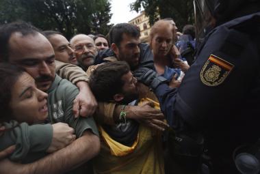 Španělská policie brání lidem v přístupu do hlasovací místnosti v Barceloně