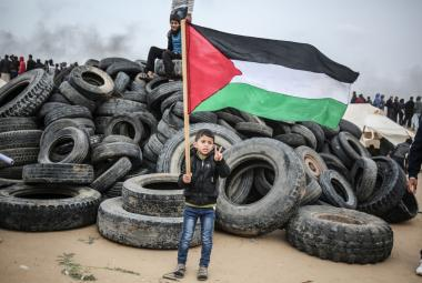 Chlapec s palestinskou vlajkou u hromady svožených pneumatik v rámci protestů na hranici Pásma Gazy s Izraelem