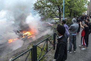Imigranti sledují zapálená auta na předměstí Stockholmu