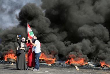 Demonstranti si fotí selfie před zapálenými pneumatikami v Bejrútu