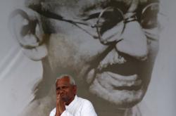Indický aktivista před Gándhího podobiznou