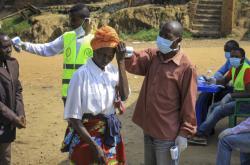 Lidé, kteří přecházejí hranici mezi Kongem a Ugandou, musí projít testy