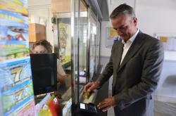 Generální ředitel České pošt Roman Knap předvádí, že se na pobočkách dá platit kartou
