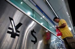 Symboly jüanu a dolaru ve směnárně v Šanghaji