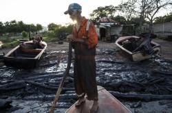 Rybář na pobřeží ropou znečištěného jezera Maracaibo