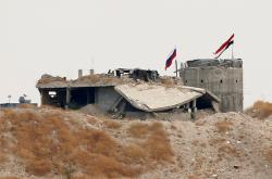 Ruská a syrská vlajka u severosyrské vesnice Zor Magar