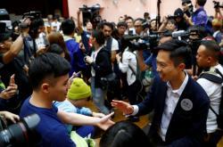 Prodemokratický kandidát Kelvin Lam slaví ve volebním štábu zisk mandátu