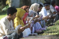 Lidé se modlí u masových hrobů obětí tsunami v Indonésii