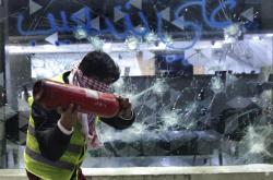 Jeden z Libanonců ničí výlohu banky