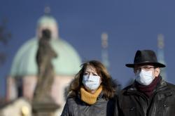 Lidé s rouškami na Karlově mostě v Praze