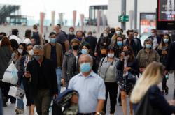 Lidé s rouškami v obchodní čtvrti La Défense ve francouzském Nanterre