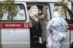 Pacientka s podezřením na covid-19 opouští sanitku