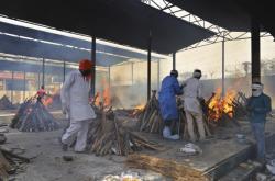 Pracovníci indických úřadů zapalují ohně s nakaženými
