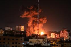 Plameny a dým nad budovami v Gaze